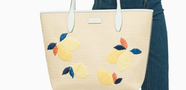 woman carrying straw kate spade tote with lemon theme